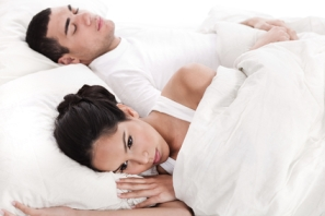 Couple in bed, men sleeping and woman lying disappointed